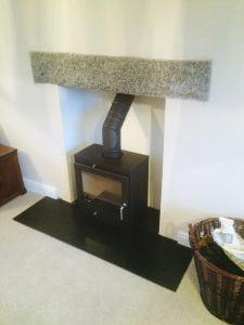 Pevex X60 - silver granite lintel, 2 piece riven slate hearth, float render finish