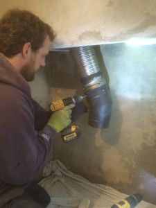 Damian fixing a section of flue pipe onto the adapter that connects the flexible flue liner
