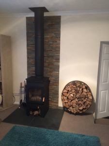 All components of the twin wall flue were painted with stove paint to match the stove. A bespoke log holder was fabricated and split face tiles were added to the wall
